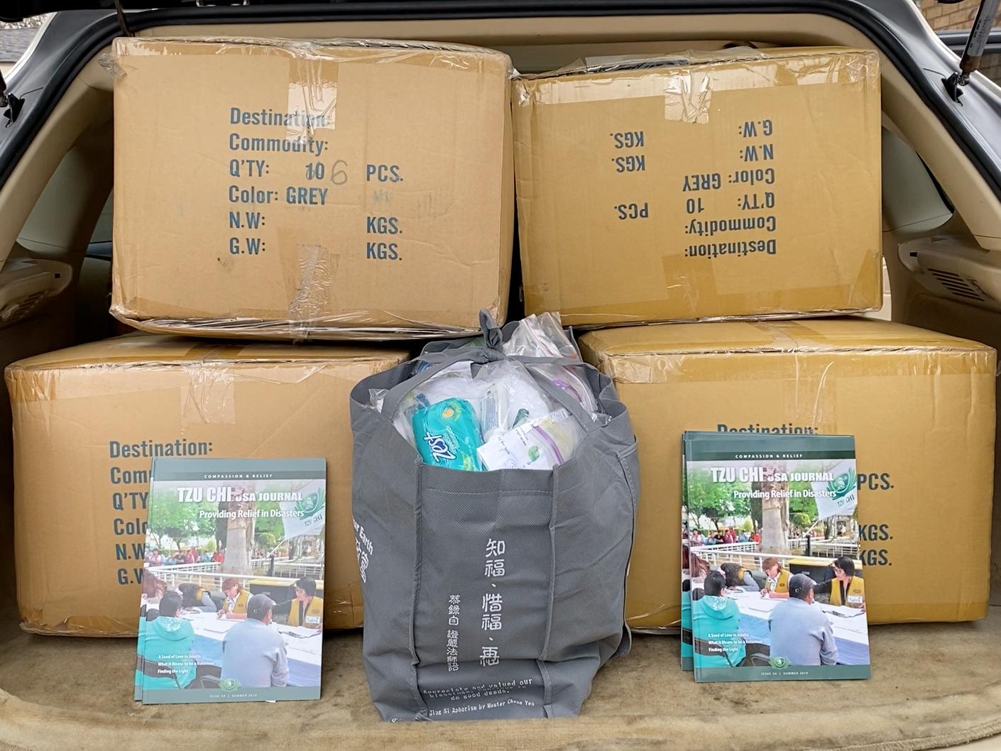 6X5VG2Laa  Embarcando las cajas llenas de mantas ecológicas y otros suministros esenciales en el  automóvil. [Foto: Yahmei Hsieh]