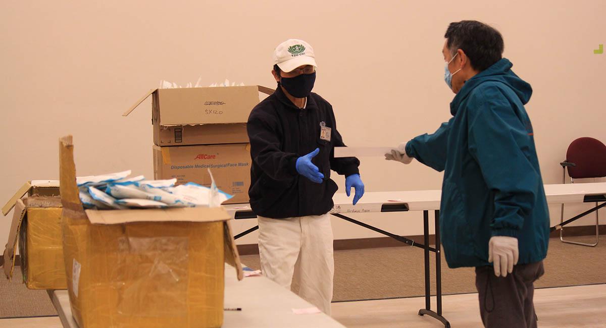 分配物資裝箱時,志工不忘保持社交距離。攝影/項才容