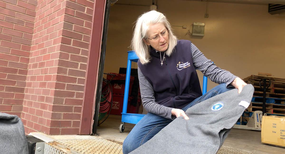 志工和接收人員解釋這些環保毛毯的由來後,接收物資的女士驚訝地看著毛毯,愛不釋手。攝影/馬樂