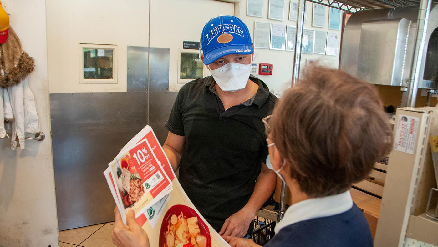 志工和老板解说素食的好处和素行动联盟的意义。摄影/林书贤