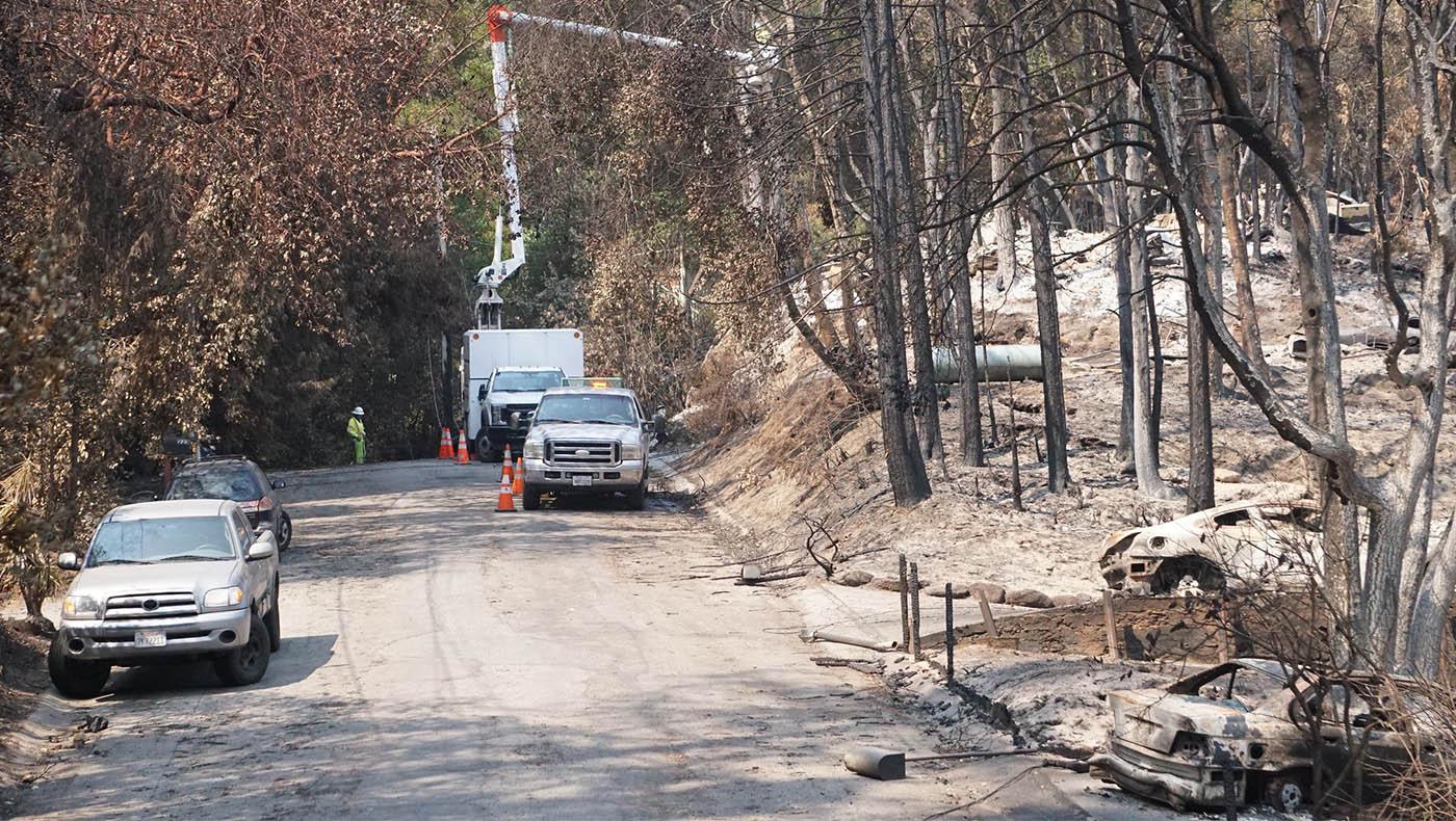 Con los incendios ahora controlados, los vehículos que trabajan pueden ingresar al área con cuadrillas para limpiar árboles y escombros que bloquean el paso o corren el riesgo de caer a la carretera. Foto Judy Liao.