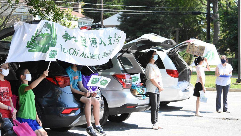 """家长把自家车后车厢打开,当作发放的""""桌子""""。摄影/蔡蕙菁"""