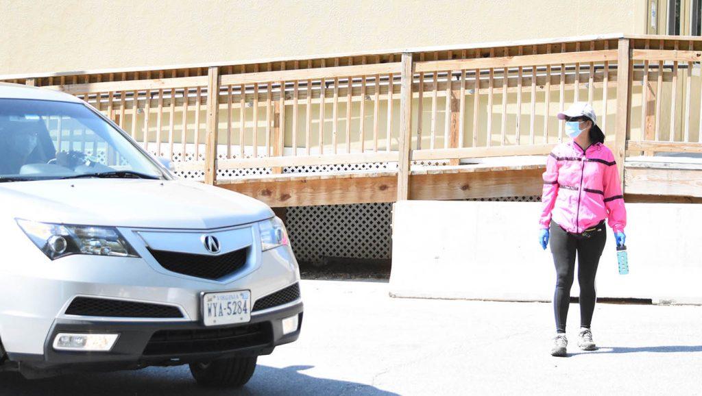 志工赖燕玲帮忙依序引导车辆前进领取书本教材或制服。摄影/蔡蕙菁