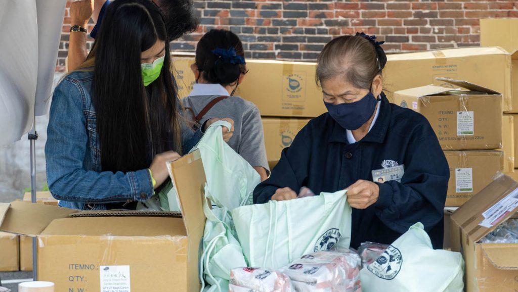 志工将香积饭、香积面、布口罩装进袋子里,准备发放给灾民。