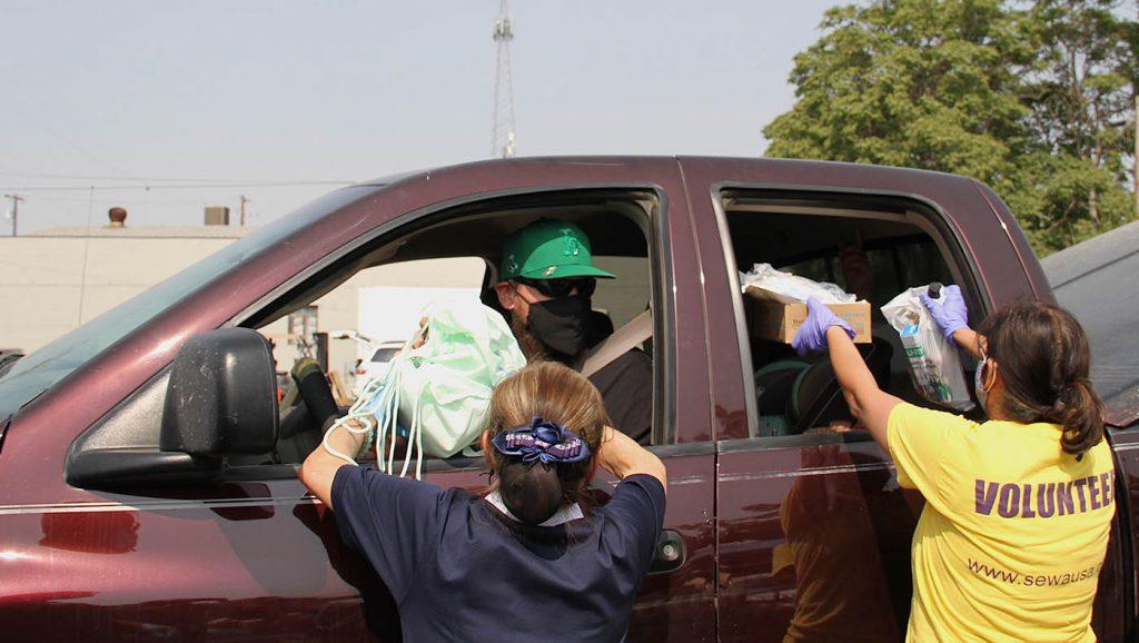 慈济志工向北部综合山火灾民发放毛毯与香积饭等物资。