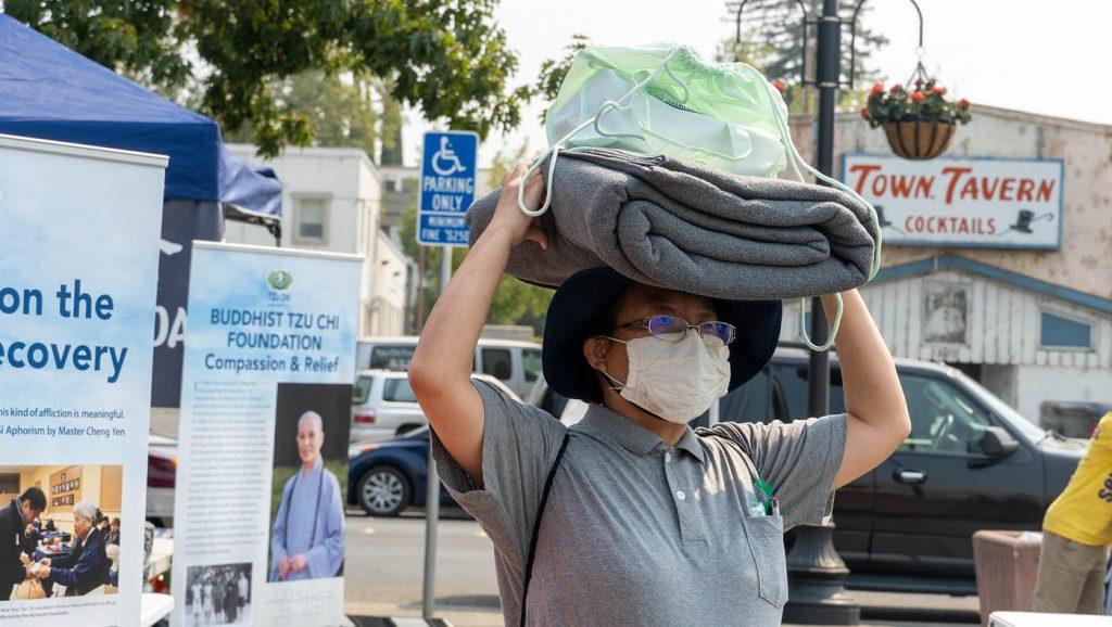 慈济志工向北部复合山火灾民发放毛毯与香积饭等物资。