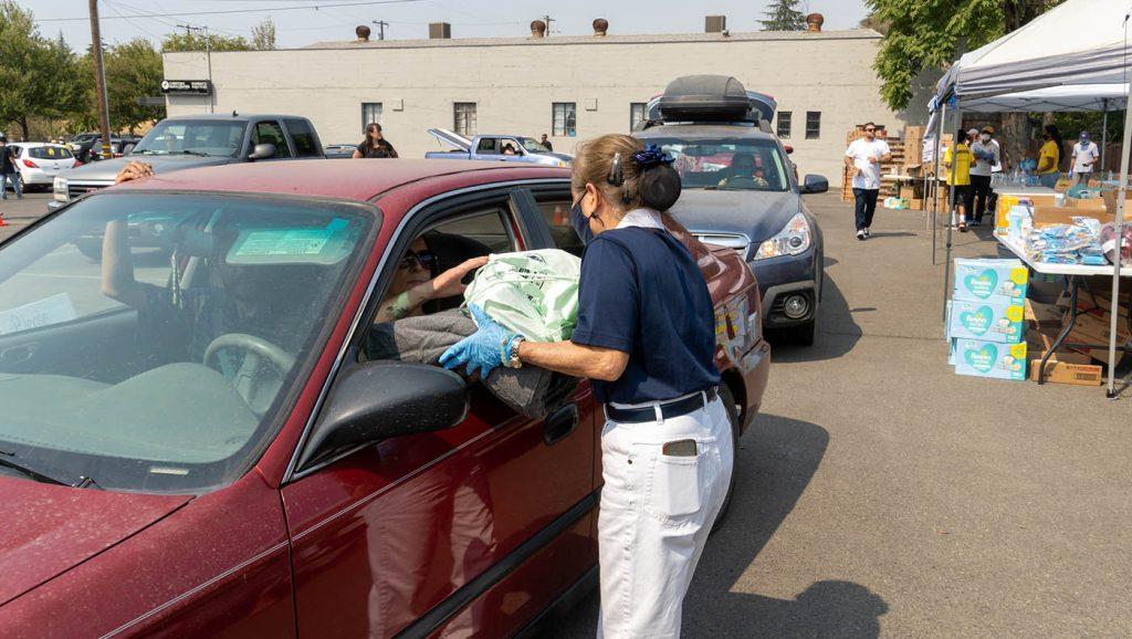 慈济志工向北部综合山火灾民发放毛毯与香积饭等物资。摄影/曾奂珣