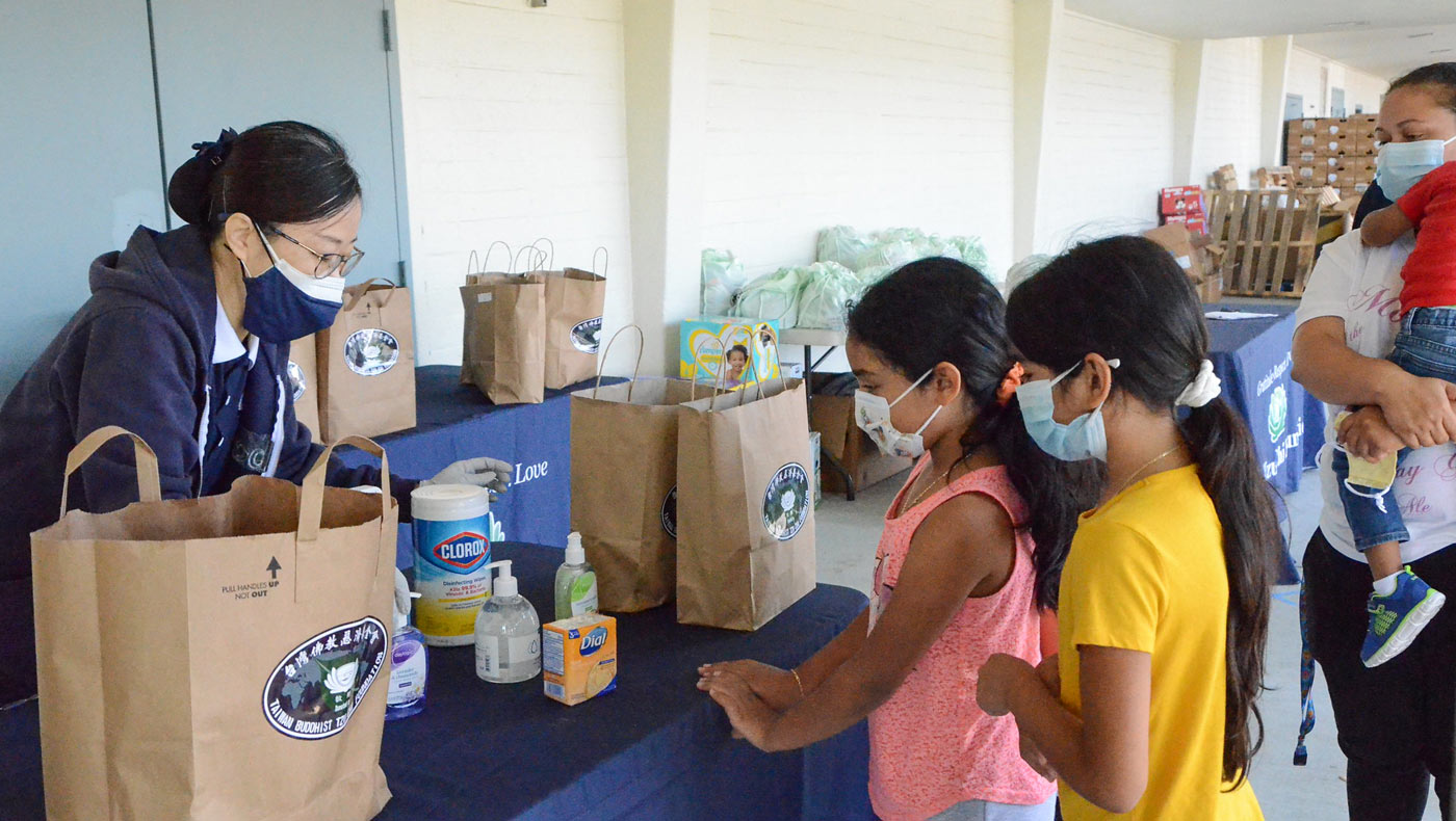Tzu Chi volunteer Emily Polivka reminds families to keep sufficient air circulating in their homes when using the cleaning products they received. Photo/Vivian Chang