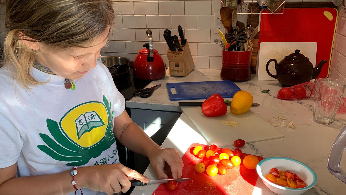 麦安娜(Ana Miner)帮妹妹麦瑞娜(Serena Miner)切菜。图片来源/华府慈济分会