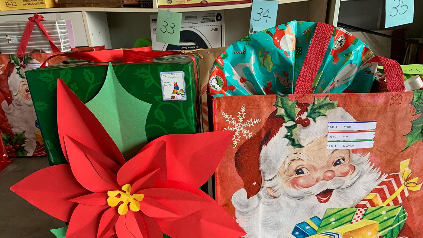 志工施藹珊及吳佩施把同一個家庭包裝完畢的禮物裝袋綁在一起,並在禮物袋上貼上禮物收件人的名字及編號,便於十二日當天的發放。攝影 /謝琇茹