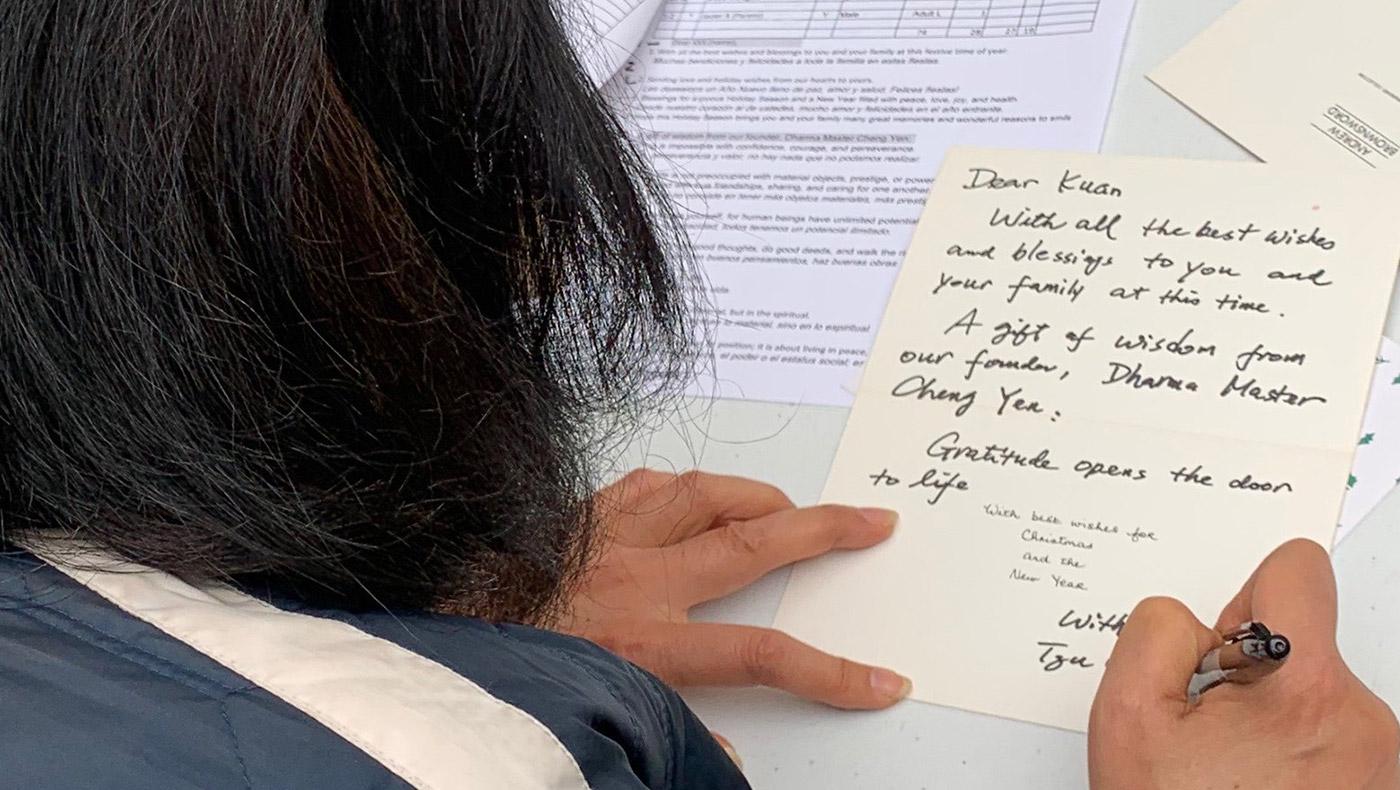志工以英文或西班牙文親筆書寫聖誕卡,除了祝福語,還有一句證嚴法師的靜思語,鼓勵他們勇敢的面對困難、堅持下去。攝影/謝琇茹