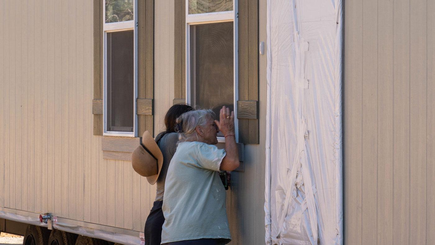 終於親見未來的家,薩曼莎與婆婆靠在窗前,試圖一探房子內部設計。攝影 / 曾奐珣