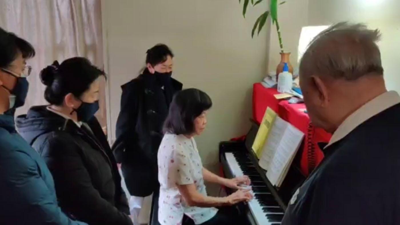 資深志工楊景舜(右),志工探訪時,楊太太用變形的手指彈奏出美妙地樂曲,讓人讚嘆。攝影/蘇煜升