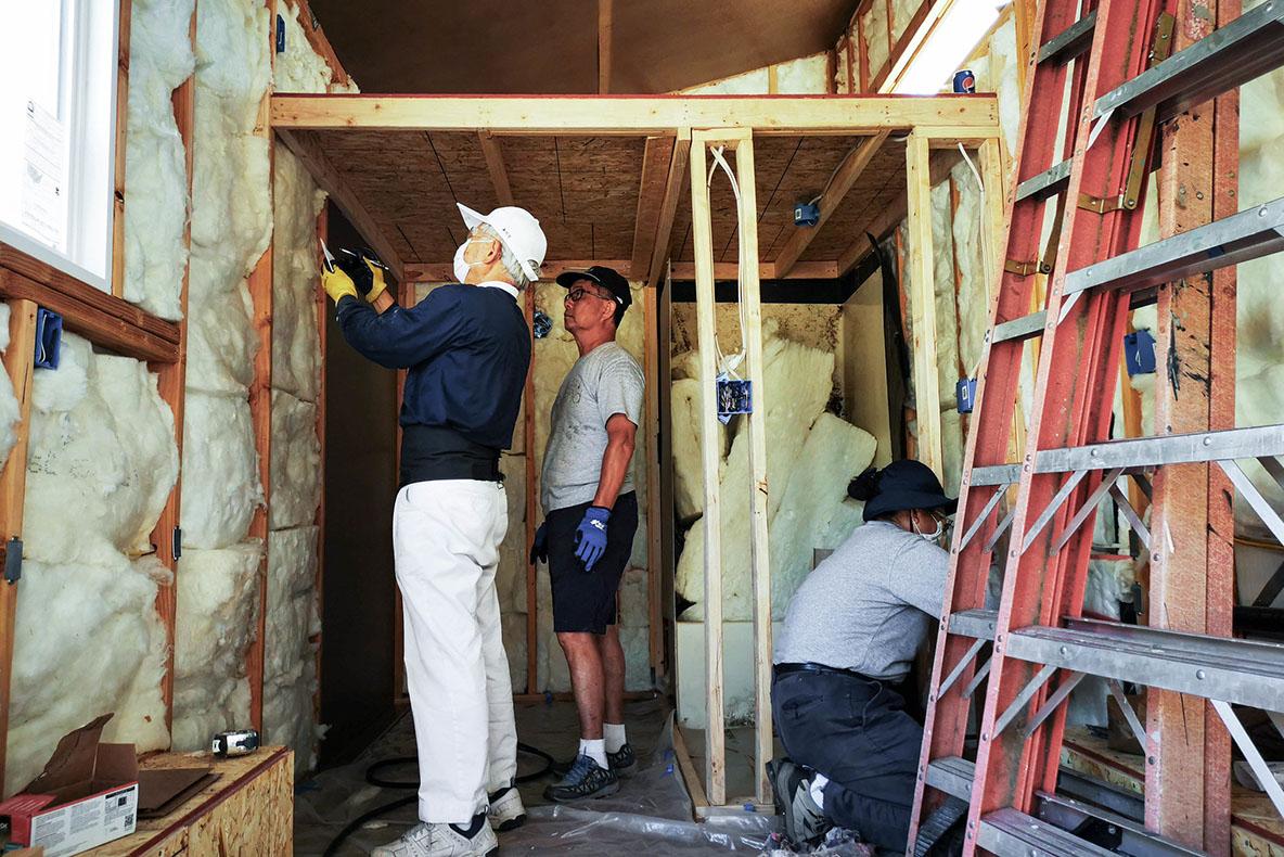 具備不同技術能力的慈濟志工在建築工地裡,按照艾麗莎·諾蘭的指示,操作著各項任務。拍攝/曾奐珣