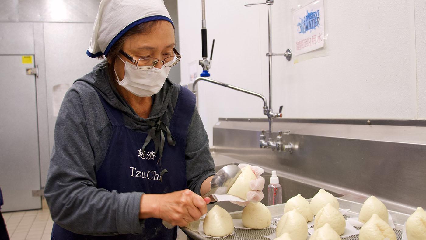 志工用湯匙壓出壽桃的形狀。攝影/劉翰卿