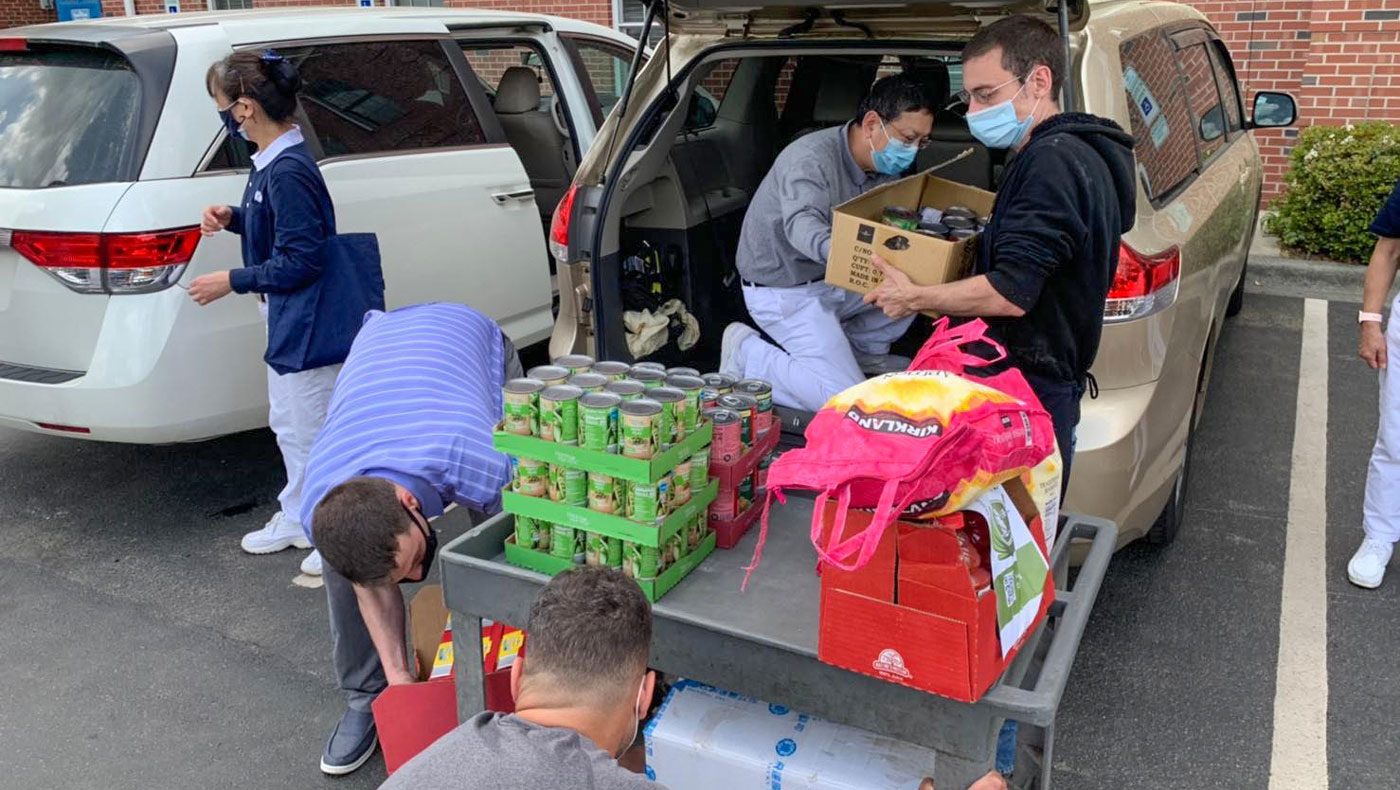Volunteers from both Tzu Chi and Durham Rescue Mission carry canned food together. Photo/Yung Shih Huang