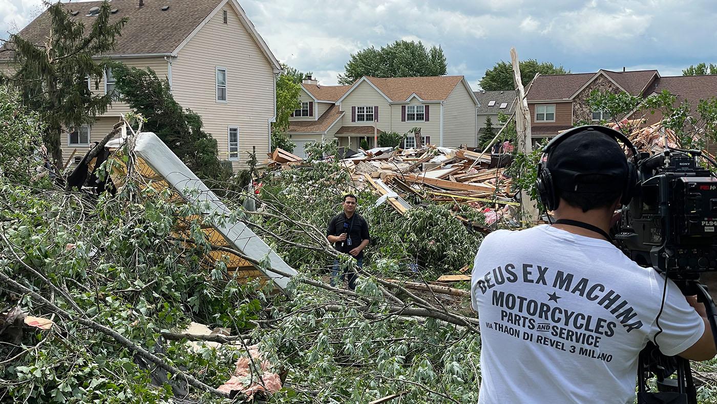 新聞記者站在屋子的殘骸中播報。攝影/馬樂