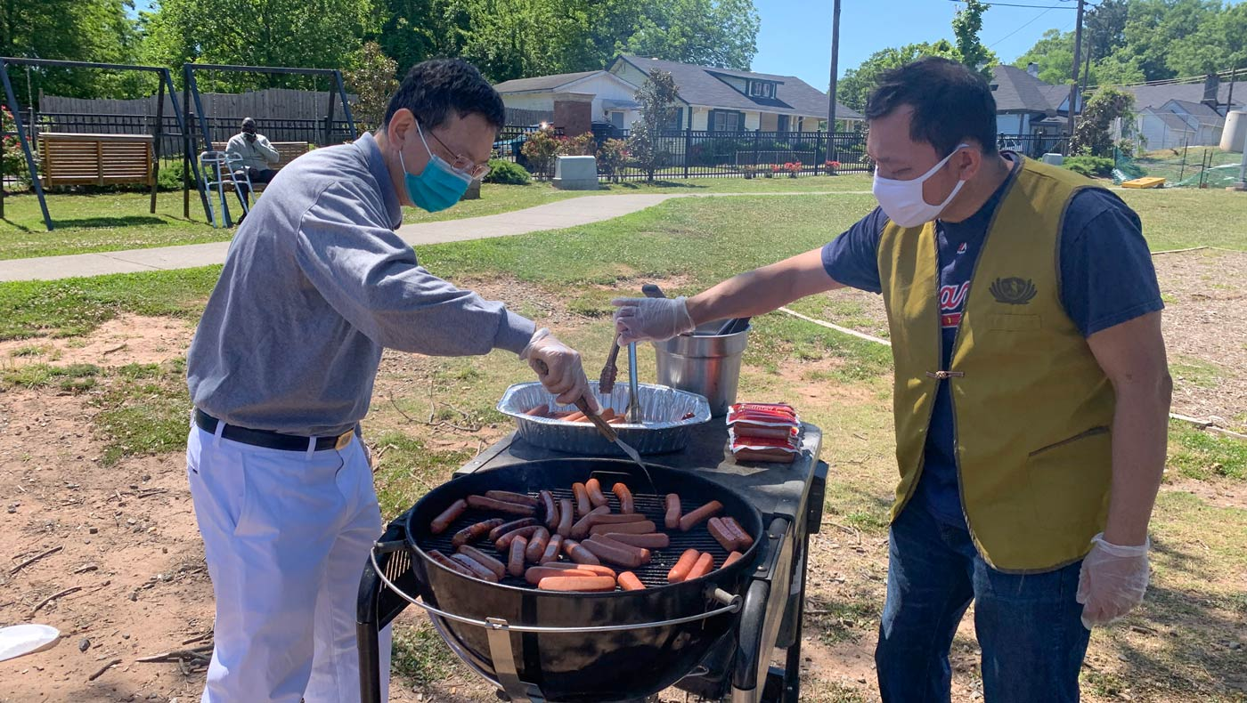 Jyhshing Chen (left) and Phooiseng Lim (right) place packs of vegetarian hot dogs on the grill. Photo/Yungshih Huang