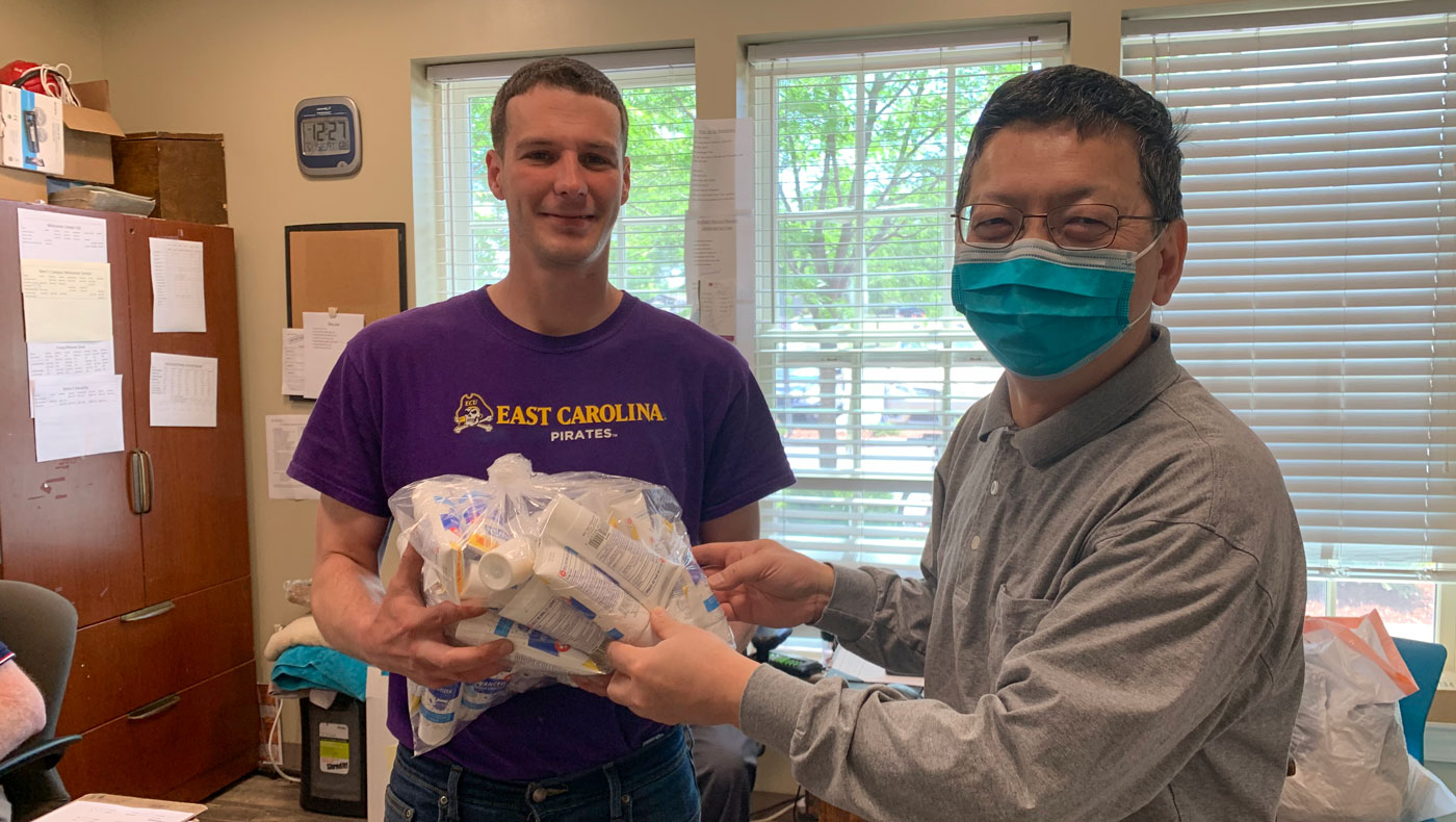 Jyhshing Chen (right), in charge of this meal service event, donates hand sanitizers to the Durham Rescue Mission on behalf of Tzu Chi USA. Photo/Yungshih Huang