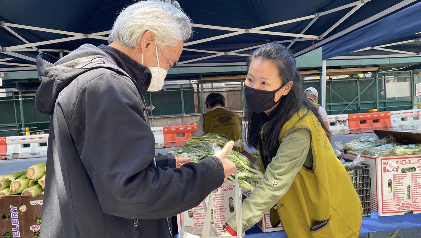 劉立欣(右)因為母親是慈濟志工,得知有蔬果發放的機會,熱情邀請同事們參與。攝影/翁秀春