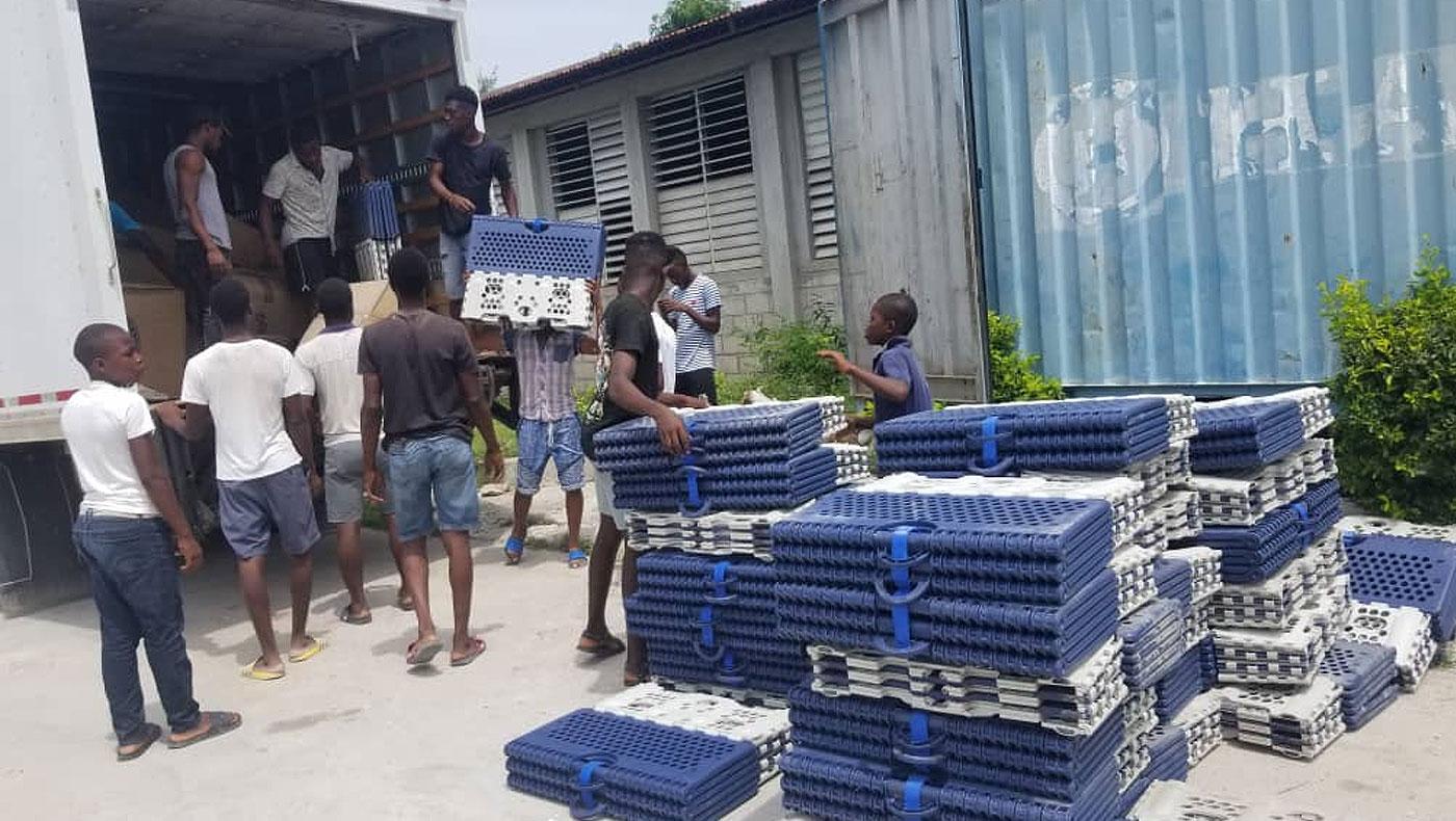 慈濟海地志工在8月29日以大卡車載滿大米和福慧床,深入重災區萊凱進行發放。