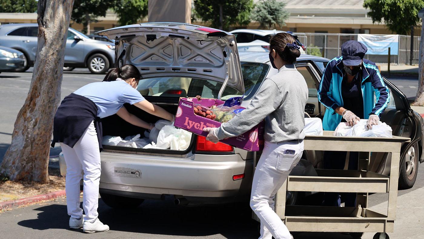 疫情嚴峻時期,東帕洛阿圖食物銀行發放改為免下車得來速方式(drive through),慈濟志工幫忙將各類食物搬到領取者的車上。攝影/呂宛潔
