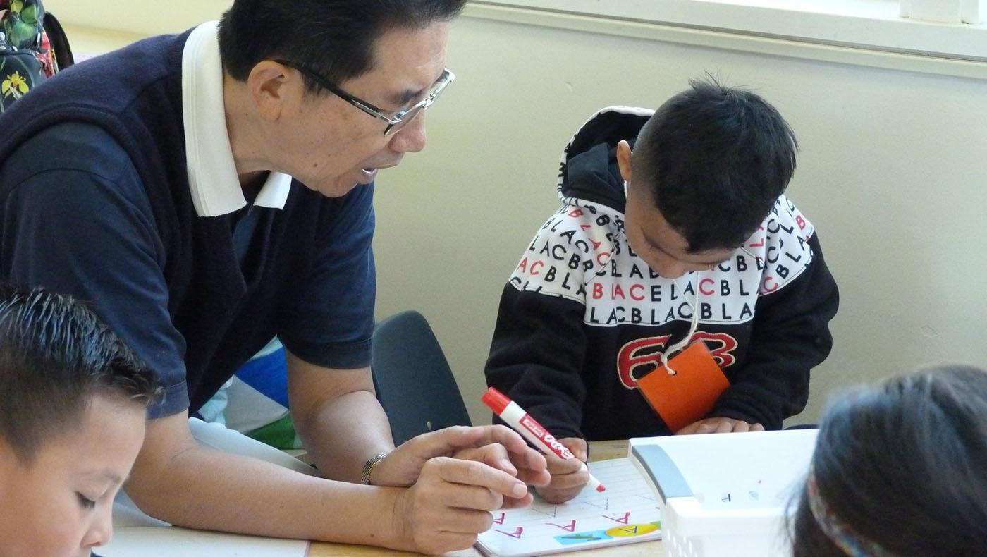 慈濟志工曹迪中擔任愛心家長,教導學生寫字。攝影/謝琇茹