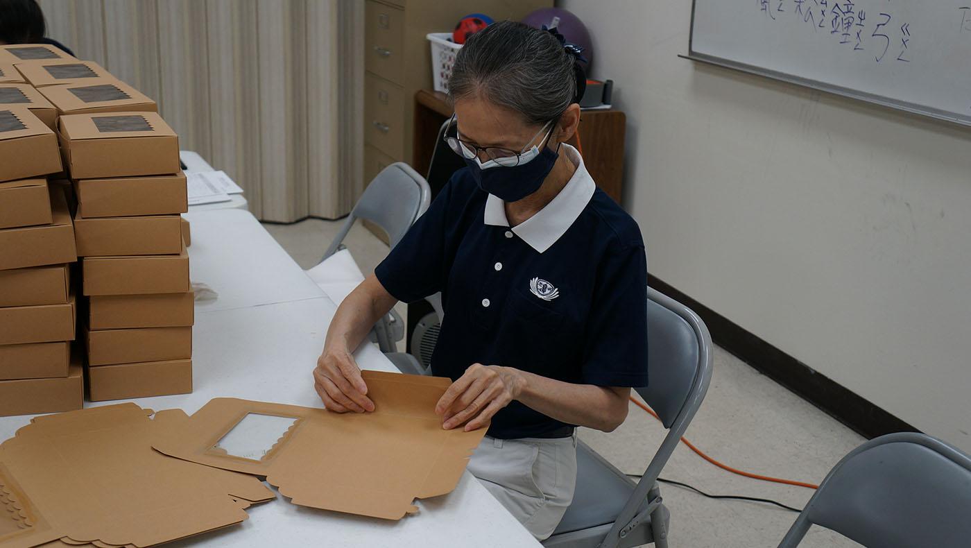志工負責協助折好裝月餅的紙禮盒。攝影/許維真
