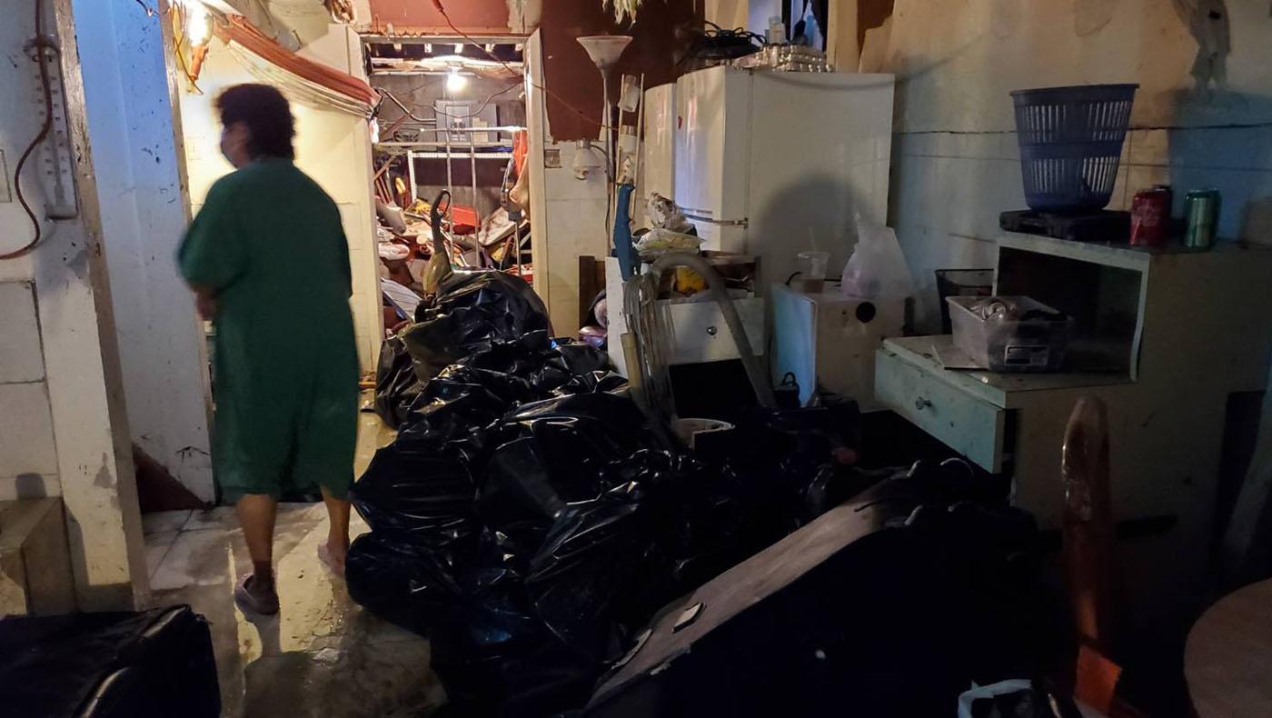 志工吳玉桂(圖左)家中地下室,全部被洪水淹没,隔天水退後的慘狀。 攝影/蔣珊珊