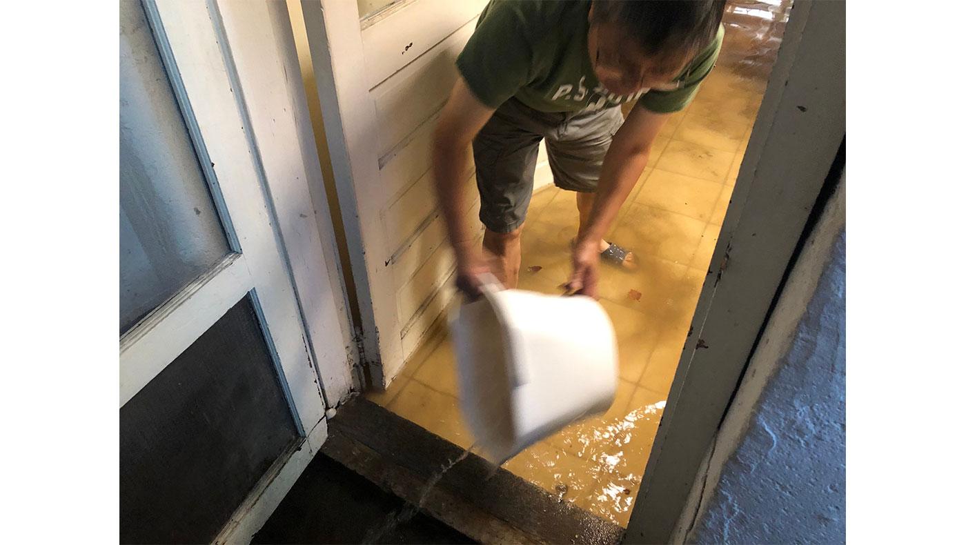 淹水隔了一夜仍未散去,沒有抽水機的情況下,只能徒手將水一桶桶往外倒。攝影/蔣珊珊
