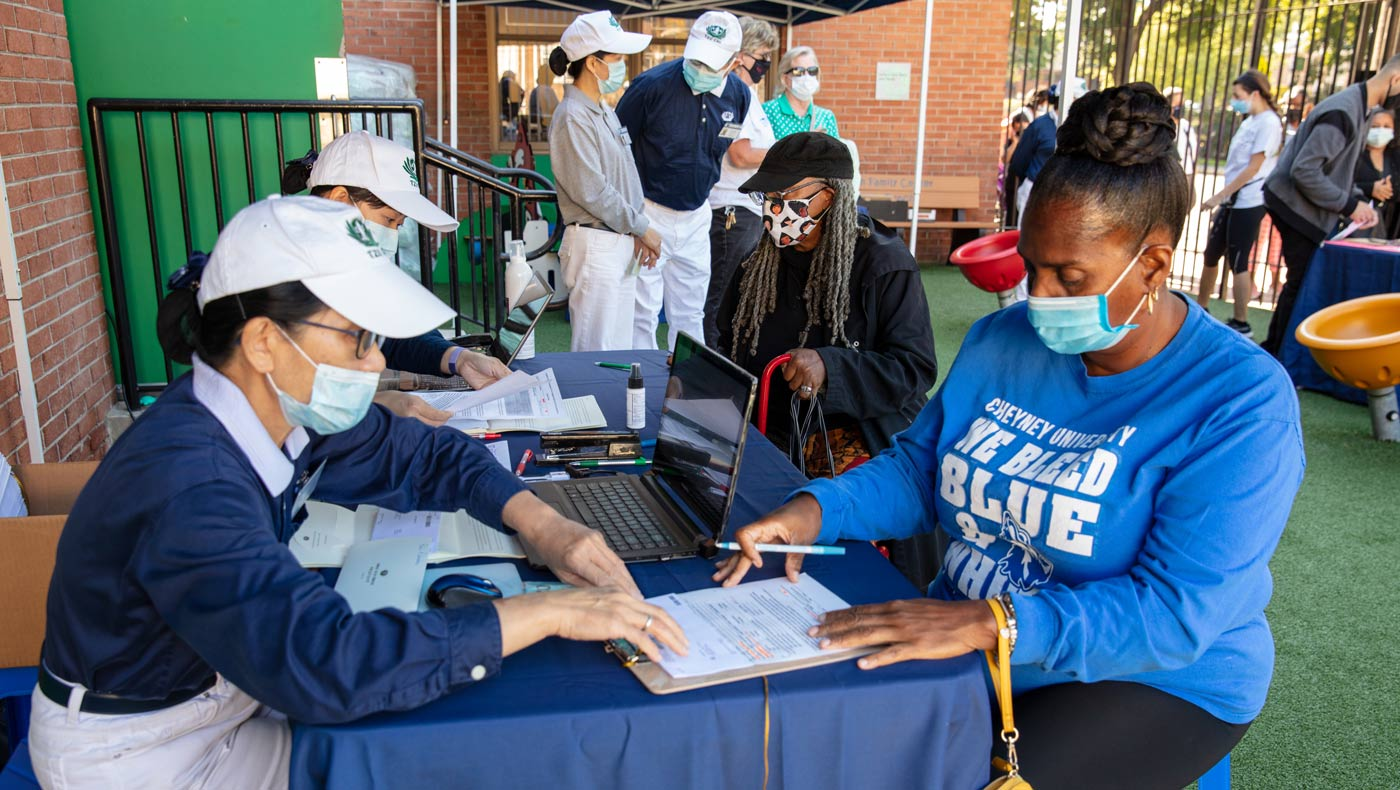 Tzu Chi volunteers verify the completeness of care recipients' information on the registration forms. Photo/Wankang Wang